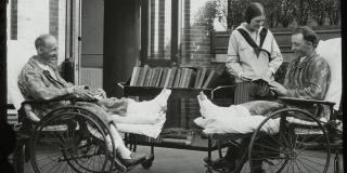 Black and white photograph of two men in wheelchairs each smiling and holding a book. A woman with a library cart stands beside them.