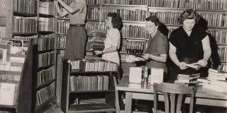 Black and white photograph of four women sorting through a library cart and stacks of books.