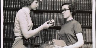 Black and white photograph of a woman wearing a headband light offering another woman a similar device.