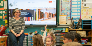 An educator sits in front of a large screen displaying NYPL's homepage and smiles to a classroom full of engaged, young students