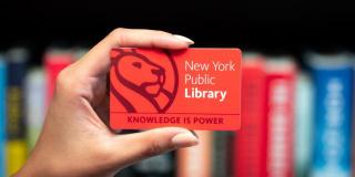 A hand holding an NYPL card in front of a row of books