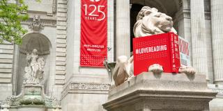 Photo of marble lion statue with a red book prop on its paws in front of the Stephen A. Schwarzman Building with a red banner that reads: 125 Years