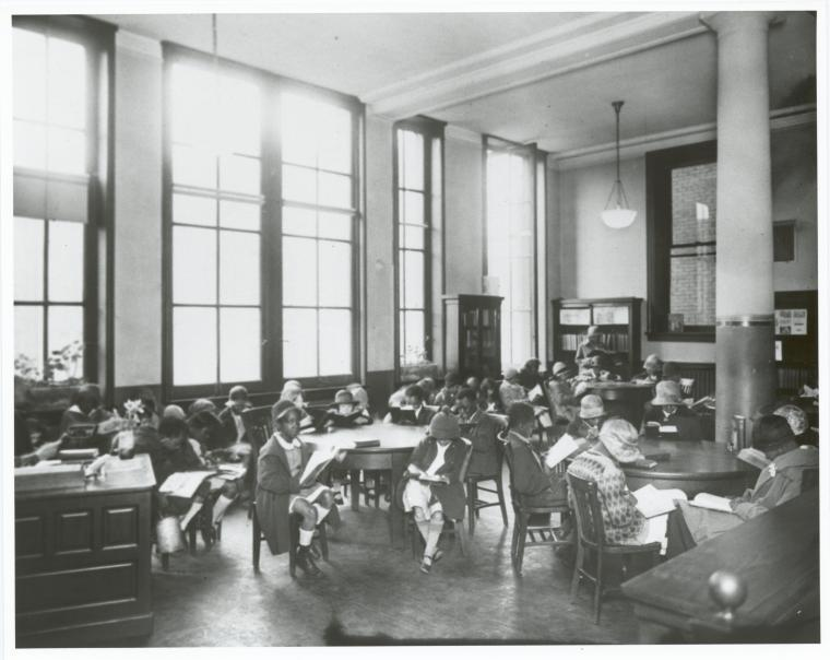 Black and white photograph of a mixed-race group of children in early dress reading in a library.