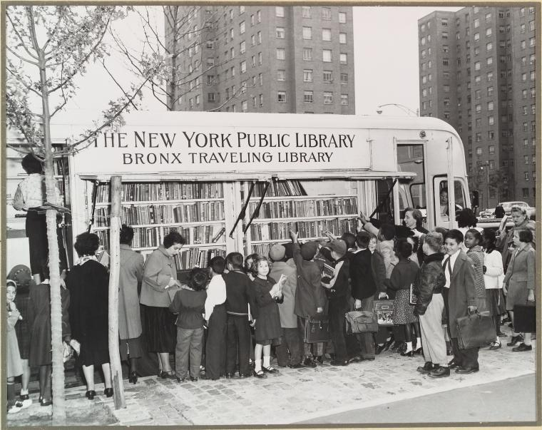 Black and white photograph of a line of children outside a bus filled with books.