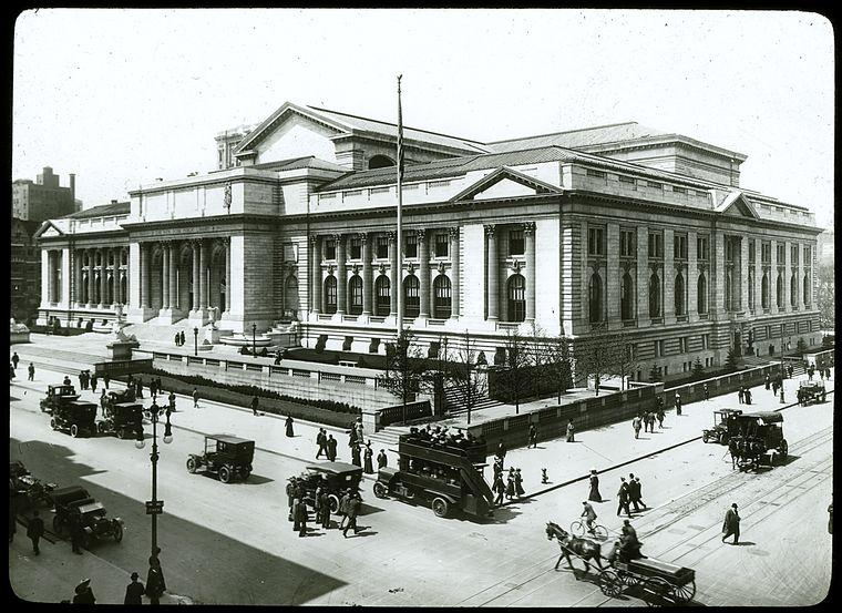 Black and white photograph of the exterior of the Stephen A. Schwarzman Building. Early 20th century cars, a double-decker bus, and a horse-drawn carriage are outside.
