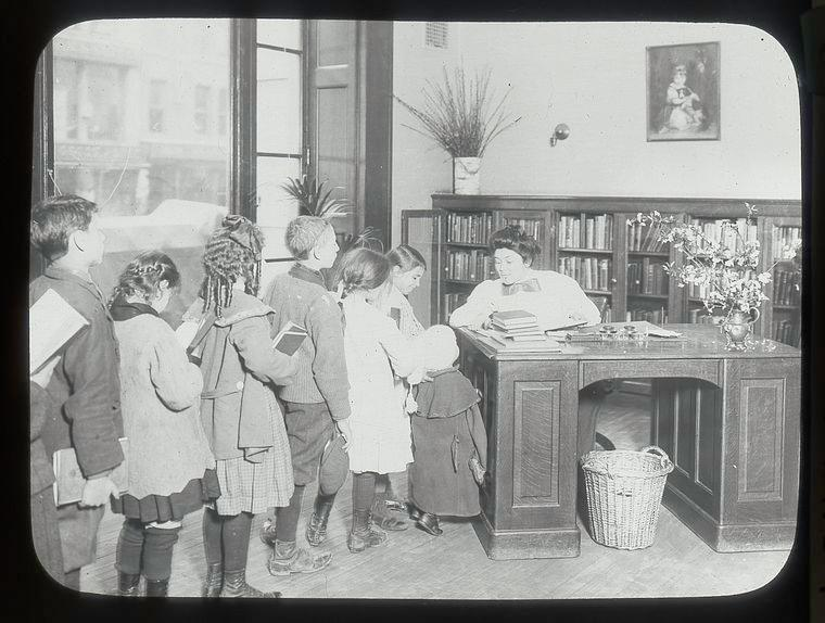 Black and white photograph sitting at a desk with a long line of children dressed in 20th century fashion.