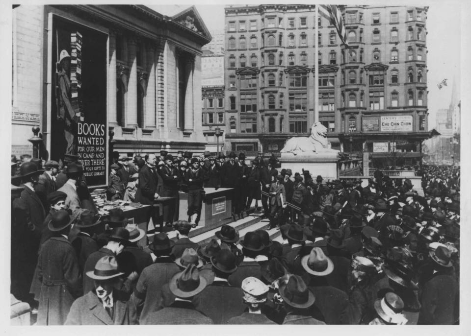 Black and white photograph of a crowd on the steps of the Schwarzman Building. A sign of a cartoon soldier reads: Books wanted for our men in camp and over there.