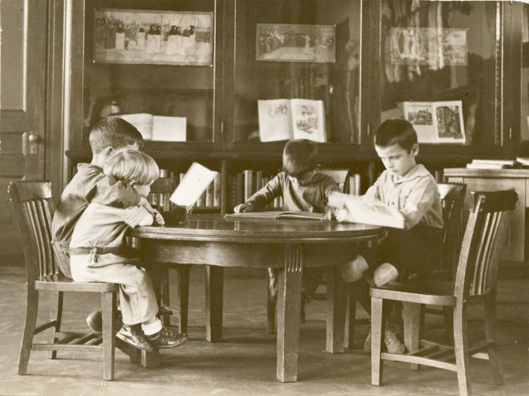 Black and white photograph of four children reading at a circular table.